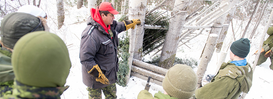 slide - Master Corporal Joe Lazarus of 3 Canadian Ranger Patrol Group demonstrates an improvised shelter to members of the Algonquin Regiment and Army Cadets from northern Ontario during Exercise MOOSE SURVIVAL in Cobalt Ontario, February 7, 2015.