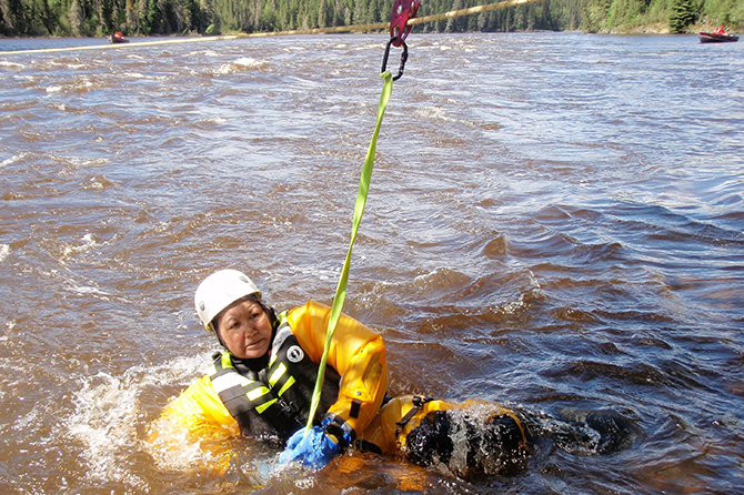 Master Corporal Kathleen Beardy of Muskrat Dam First Nation clutches a carabiner clip attached to a rescue rope during swift water rescue training at Quicksand Rapids on the Windigo River on June 21, 2017. Photo: Warrant Officer Barry Borton, 3rd Canadian Ranger Patrol Group. ©2017 DND-MDN Canada.