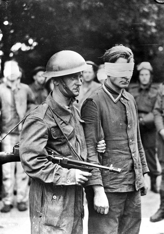 An unidentified Canadian soldier escorts a German prisoner captured during Operation JUBILEE, also known as the Dieppe Raid. England, August 19,1942.