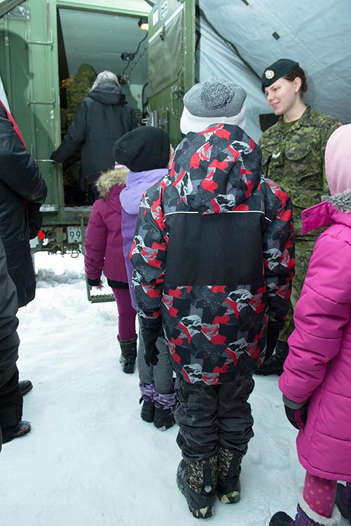 Students wait for their turn to climb aboard a military vehicle to speak with Santa, outside Radisson School, Winnipeg, Manitoba, during Operation RADIO SANTA, on December 7, 2016. 38 Signal Regiment deploys to schools with their communications equipment to establish a communications link with the North Pole so that children from Junior Kindergarten to Grade 4 can talk to Santa about their Christmas wishes.