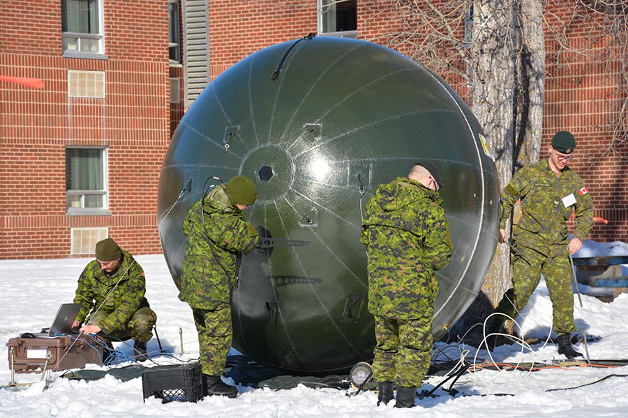 soldiers install a portable satellite system