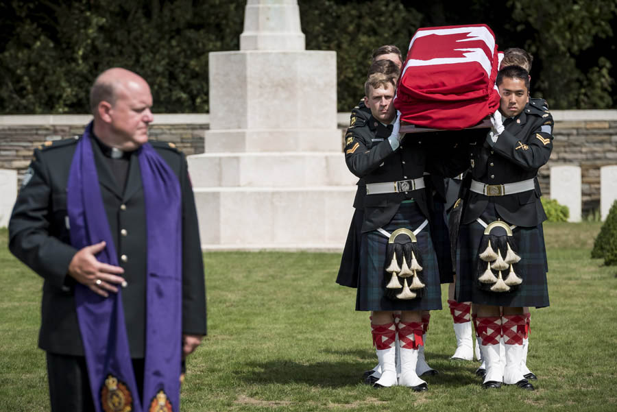 Under the direction of Padre Major Tom Hamilton, a contingent of Calgary Highlanders carry the flag-draped coffin of an unknown Canadian soldier during his interment with military honours at Canadian Cemetery No. 2 in Neuville-St. Vaast, France on August 23, 2017. Photo: Corporal Andrew Wesley, Army Public Affairs. ©2017 DND/MDN Canada.