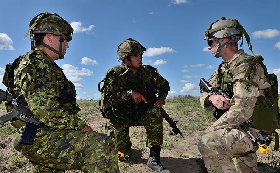 Captain Ward Lentz from the 38 Canadian Brigade Group Winnipeg Infantry Tactical Group (WITG) briefs Captain Brian Goree, United States Army and Captain Sean Hennessey (WITG) on Exercise BISON WARRIOR at Canadian Forces Base Shilo, Manitoba, on August 18th, 2015. Photo: Master Corporal Louis Brunet. ©2015 DND/MDN Canada.