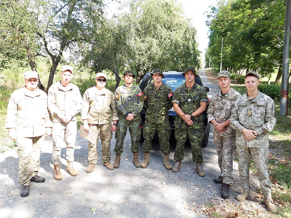 Left to right, Master Corporal Daniel Lefebvre, Sapper Pavel Klimov, and Sergeant Jean Pelletier of 5 Combat Engineer Regiment stand with several of their Ukrainian counterparts in Kamianets-Podilskyi, Ukraine in June 2019.