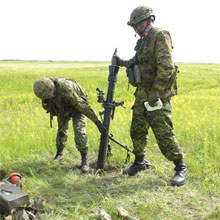 Soldiers loading an 81-mm mortar.